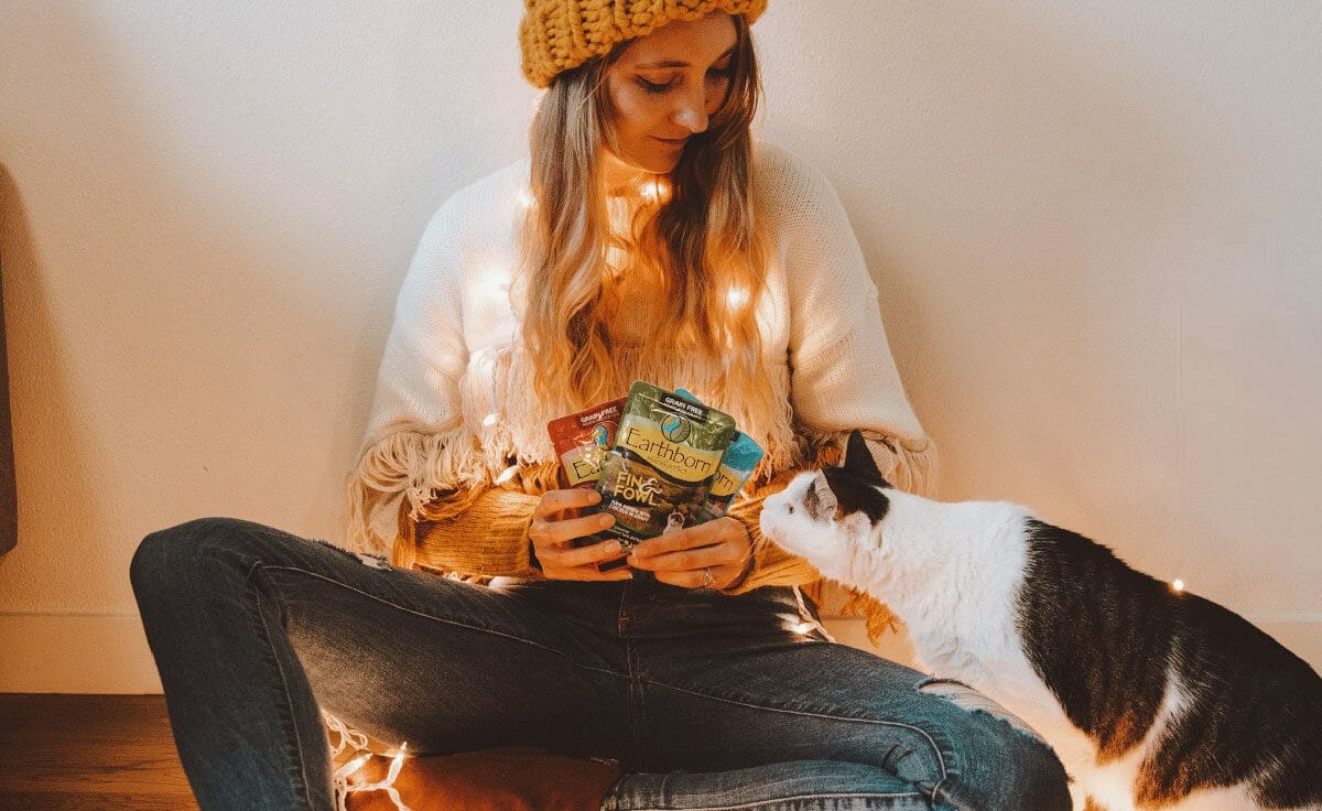 Woman holding Earthborn Holistic moist pouches with her cat trying to sniff them