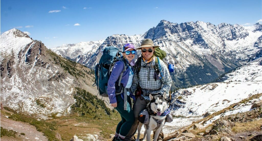 A couple and their husky stand at the top of Buckskin Pass in Colorado