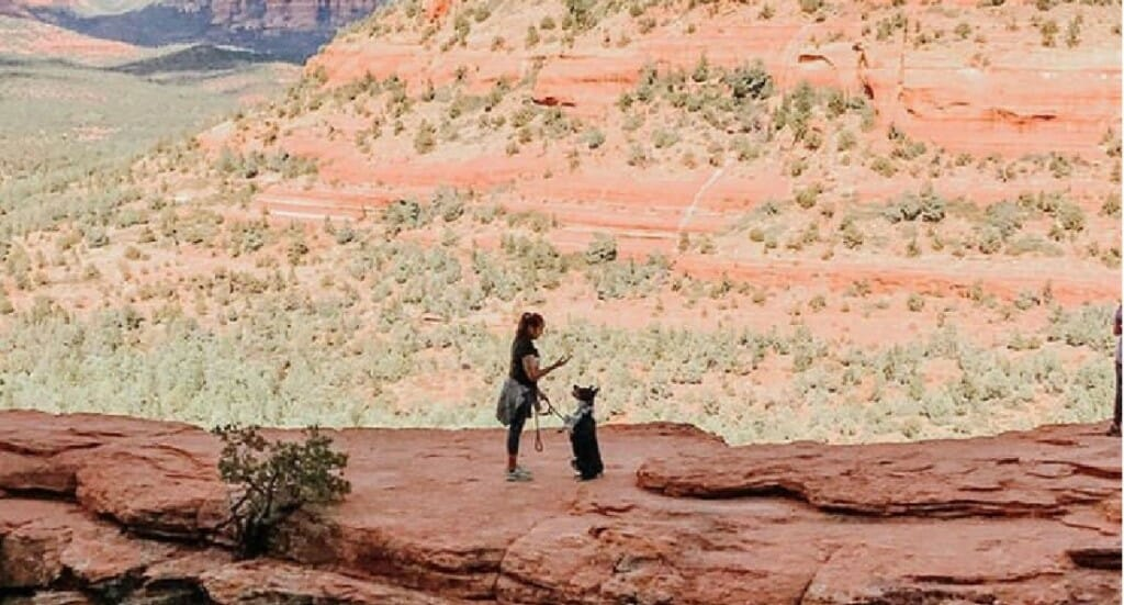 A woman and her dog stand on Devil's Bridge in Arizona