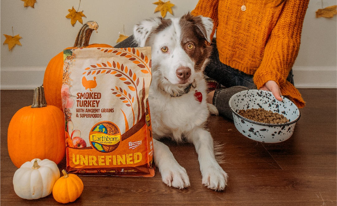 A dog sets next to a human in an orange sweater next to a bag of UNREFINED Smoked Turkey dog food