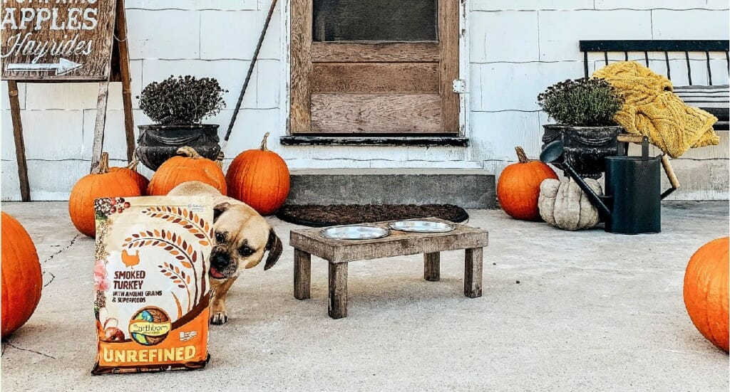 A small dog eats out of a bowl on a farmhouse porch with UNREFINED Smoked Turkey nearby