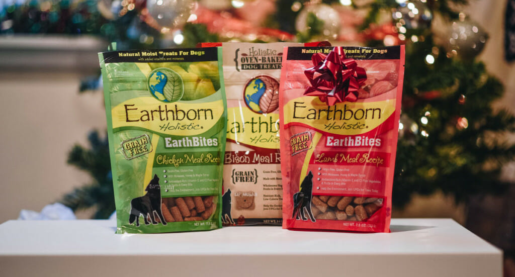 A group of three Earthborn Holistic dog treats sit on a table in front of a Christmas tree, one with a bow on it