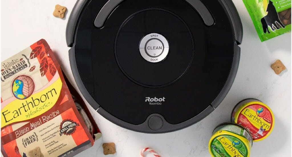 An overhead shot of an iRobot Roomba 675 with Earthborn Holistic dog treats and cat food scattered around