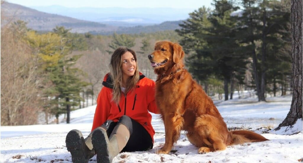 A female in a red coat sits next to her golden retriever dog in the snow with a view of mountains