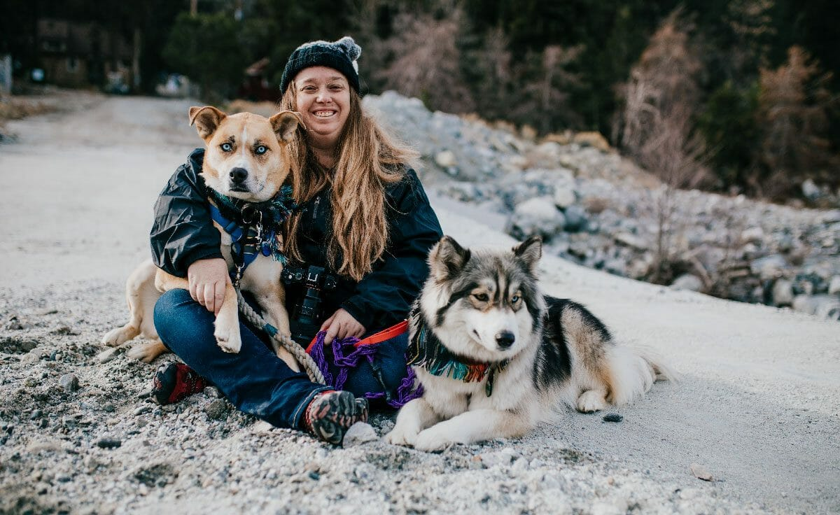 A woman and her two dogs sit together on the ground on a hike in California