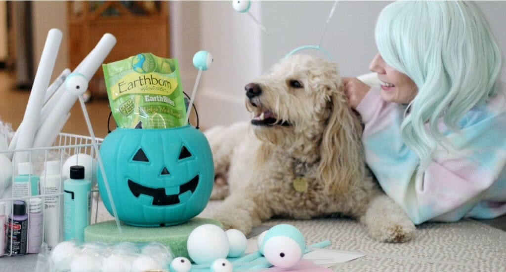 A woman wearing a blue wig lays on the floor with her dog as they create his alien Halloween costume with the help of Earthborn dog treats