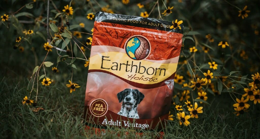 A bag of Earthborn Holistic Adult Vantage dog food sits in on the grass surrounded by yellow wildflowers