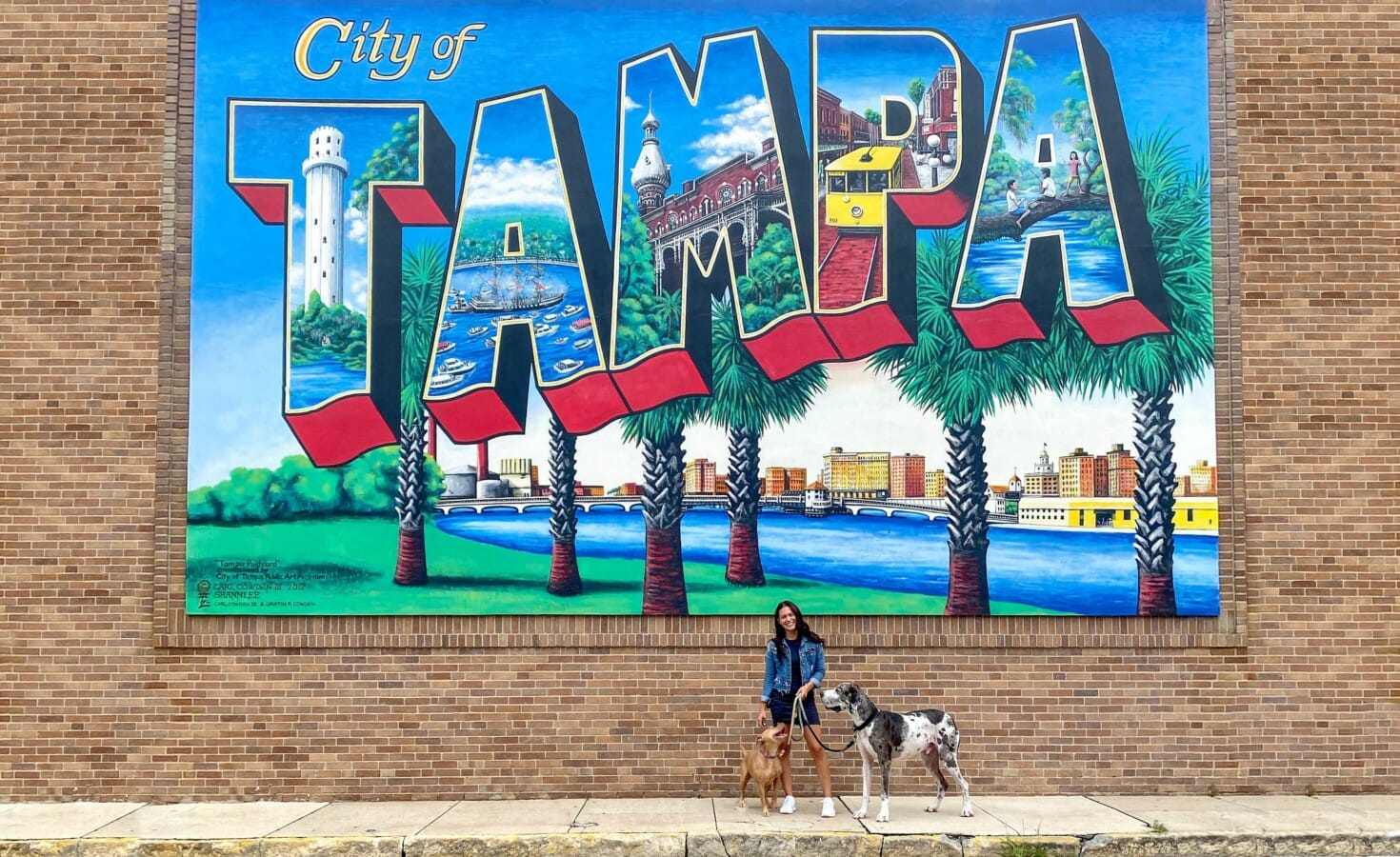 A woman and her two dogs stand in front of a City of Tampa mural