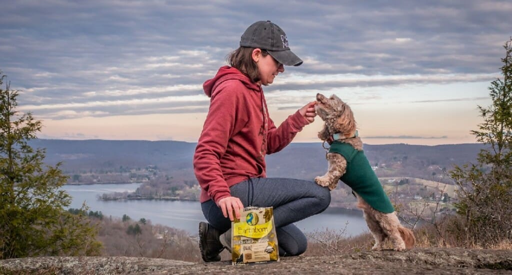 A female kneels to her dachshund mix with Earthborn Holistic dog treats on a summit