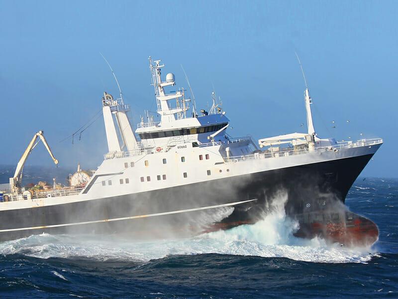 "Fishing vessel ""American Triumph"" wading through ocean waves"
