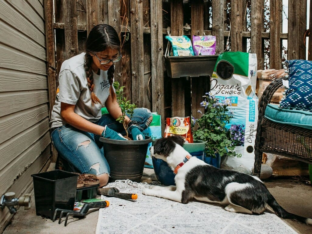Woman planting a sapling while smiling at her dog