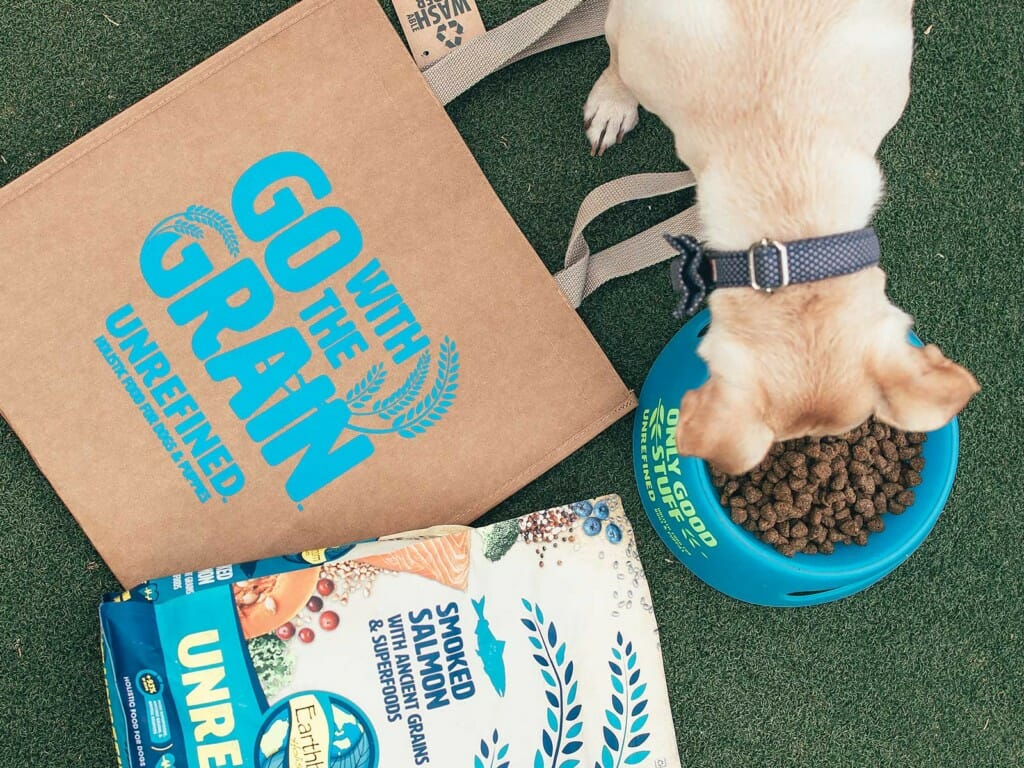 Dog eating Earthborn food next to used Earthborn packaging