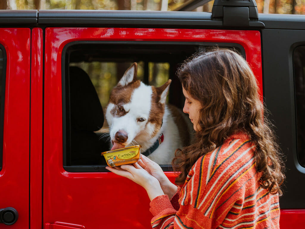 Girl holding a tub of Earthborn Holistic toby's Turkey Dinner in Gravy dog food while a dog eats from a car window