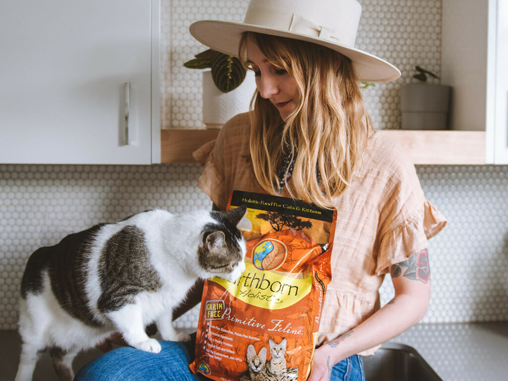 Person on a kitchen countertop holding a bag of Earthborn Holistic Primitive Feline cat food and a cat sniffing it out
