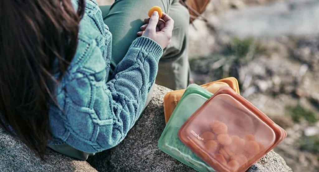 A person sits outside eating a snack out of a Stasher bag
