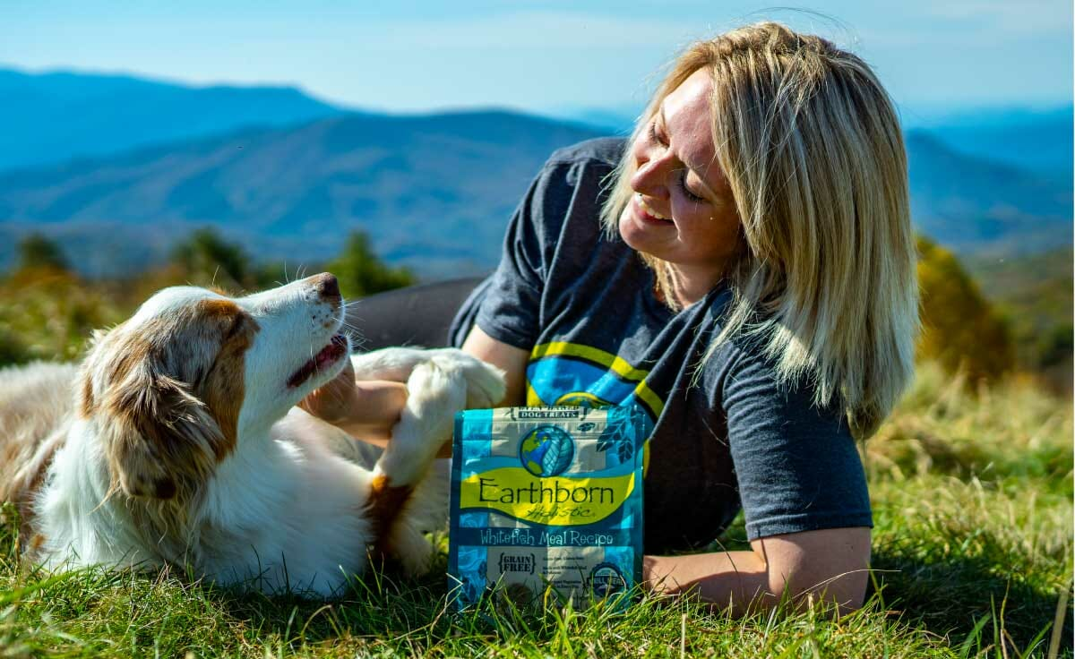 A woman lays in the grass next to her dog, feeding it Earthborn Holistic dog treats