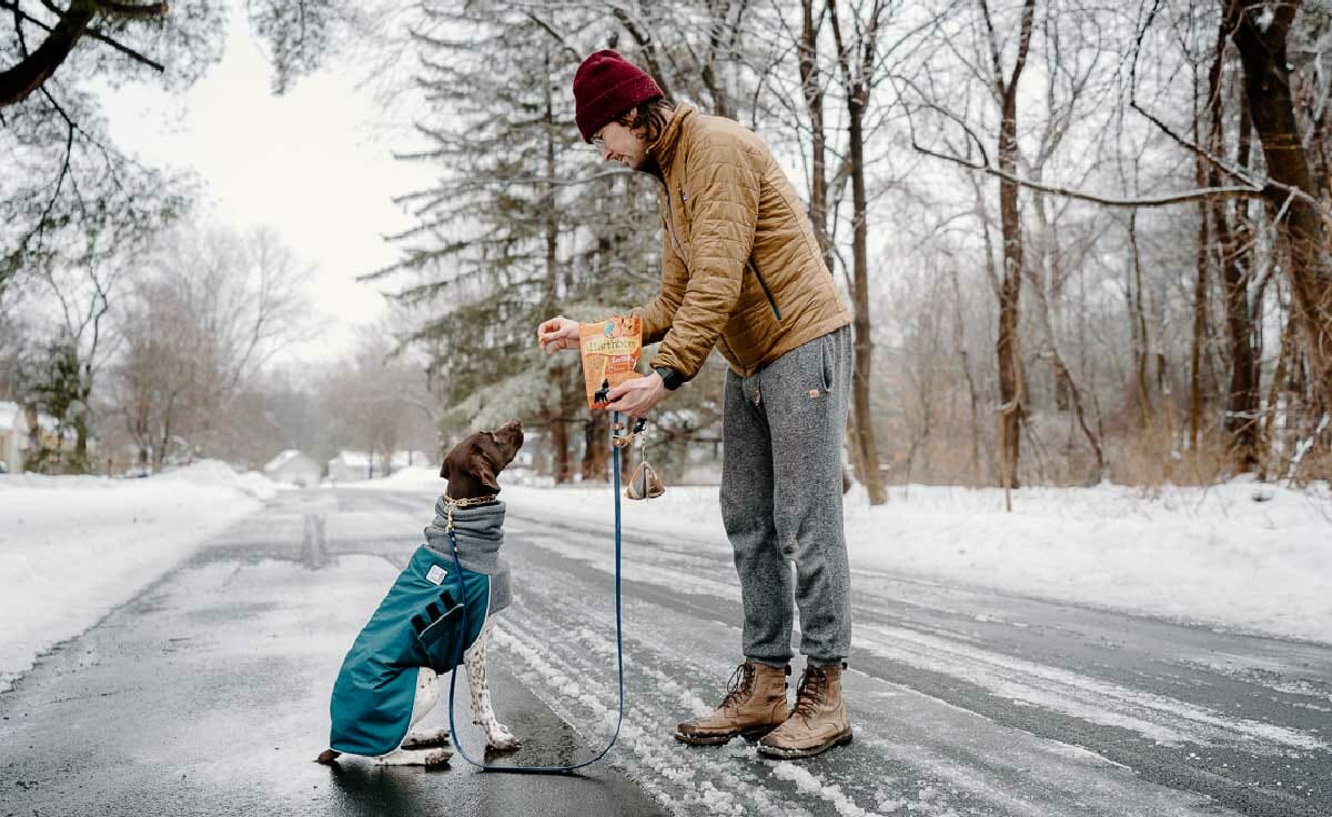 A human standing in the road feeds her dog an Earthborn Holistic treat