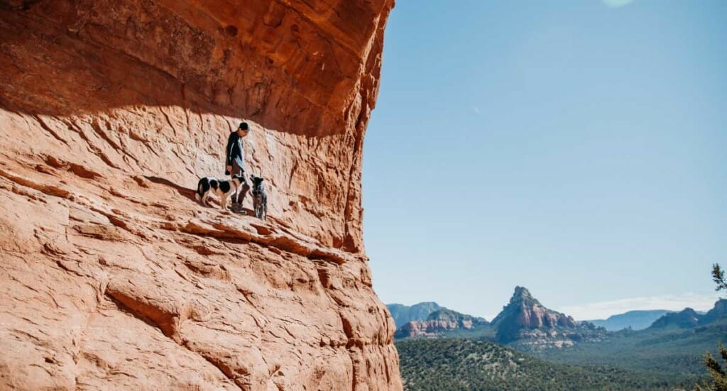 A woman and her two dogs walk alongside a cliff edge