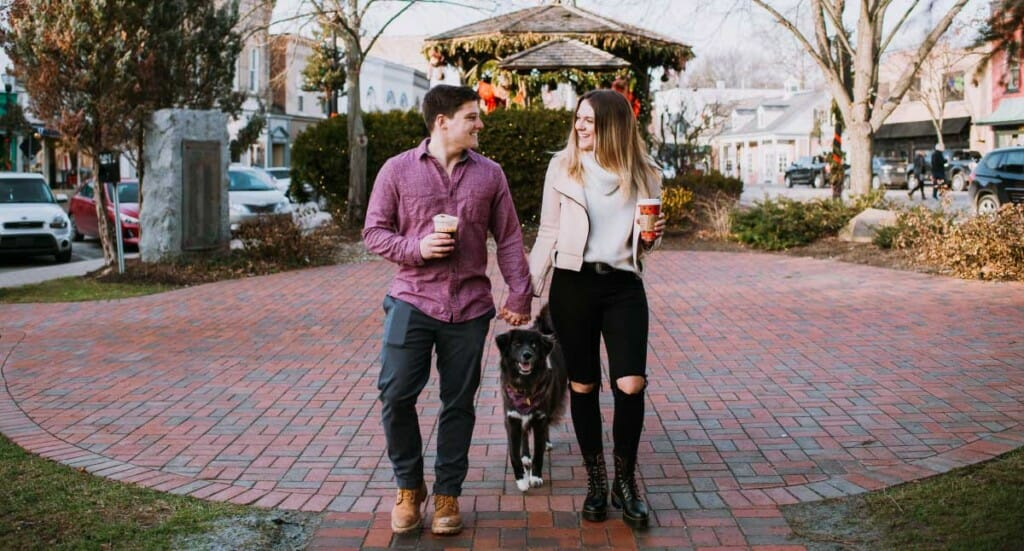 A couple walks through downtown Cleveland with their dog trailing behind