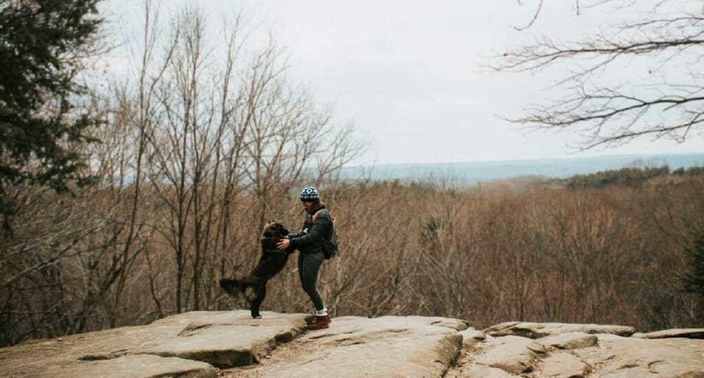 A woman and her dog stand on an overlook on a Cleveland hiking trail