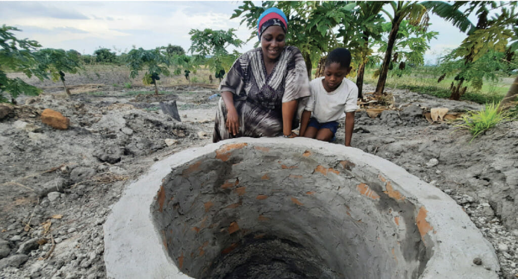 Forest garden farmer, Salma, and her son stand next to their new well