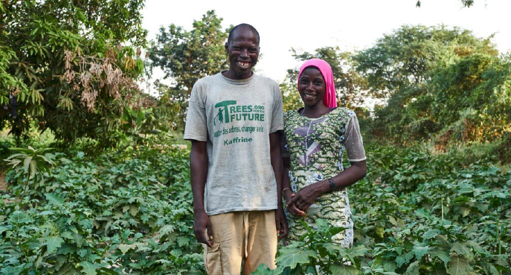 Two forest garden farmers stand in their garden