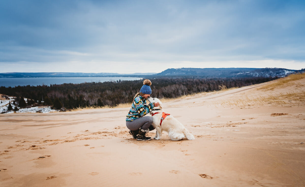 A woman and her dog sit together on an overlook
