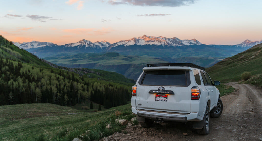 An image of a 4 Runner parked at an outlook point of a mountain range