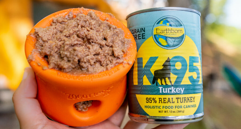 A closeup of a WestPaw Toppl toy filled with Earthborn Holistic K95. The can of K95 is held next to the toy.