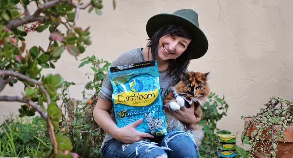 A woman holds her cat and a bag of Earthborn Holistic Wild Sea Catch cat food
