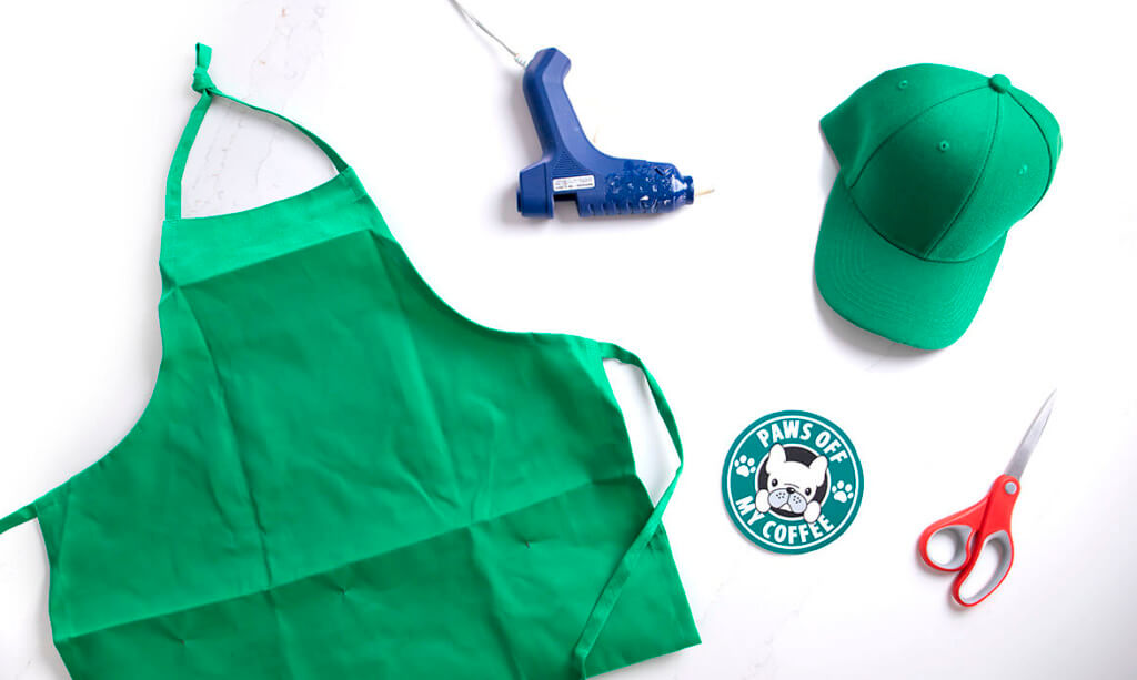 A flat lay of a green apron, hat, hot glue gun, scissors, and a coffee logo