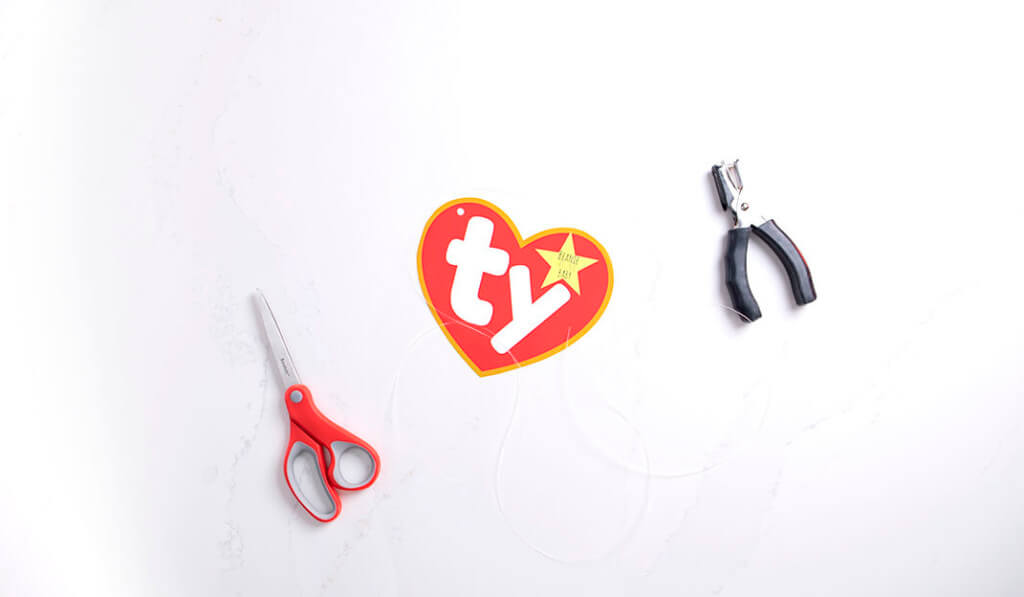 A flat lay of scissors, a hole punch, a Ty logo printout, and a piece of string