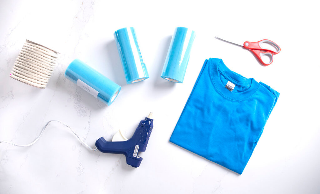 A flat lay of rope, blue tulle, a blue t-shirt, scissors, and a hot glue gun to make a DIY loofah Halloween costume