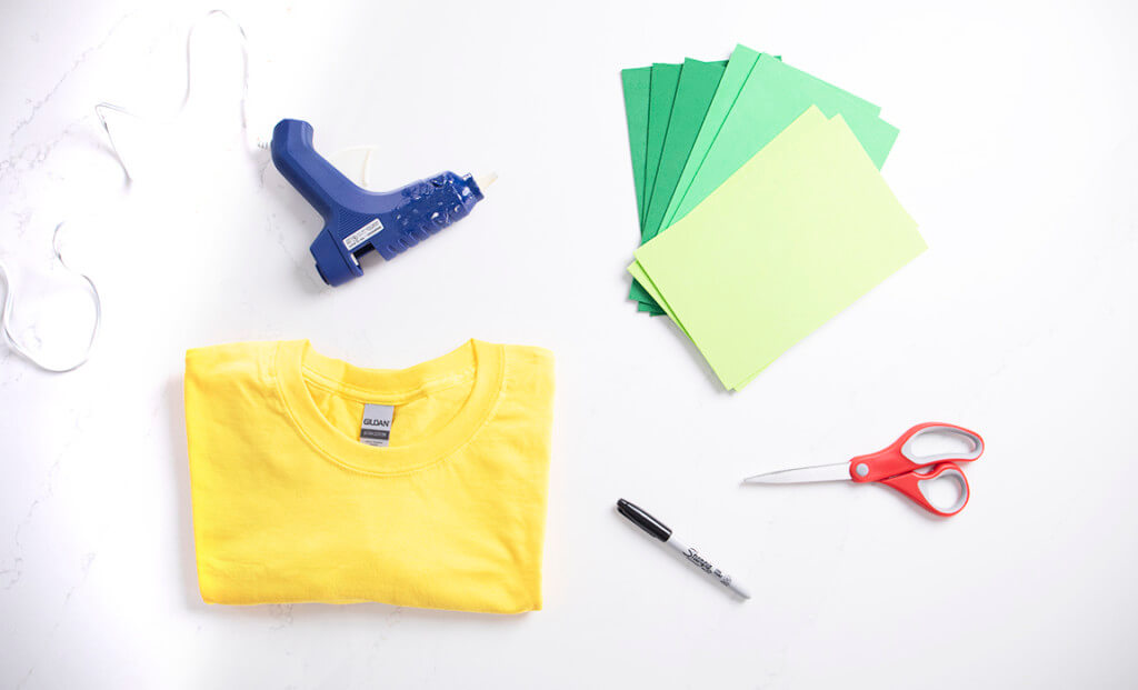 A flat lay of a yellow t-shirt, green foam, a glue gun, scissors, and a marker for a DIY pineapple Halloween costume