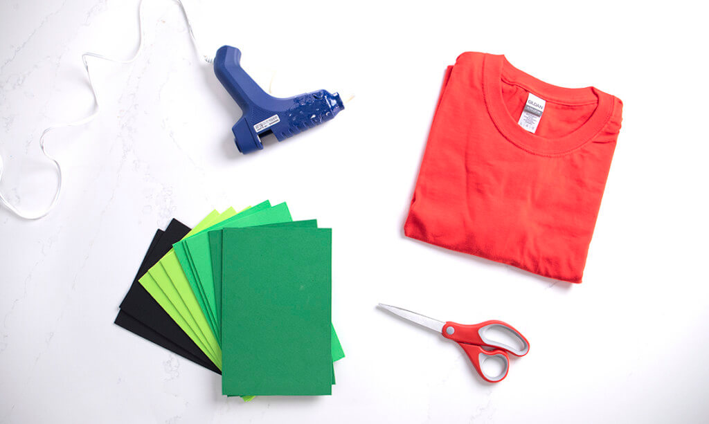 A flat lay of a red t-shirt, black and green foam, a hot glue gun, and scissors for a DIY strawberry Halloween costume